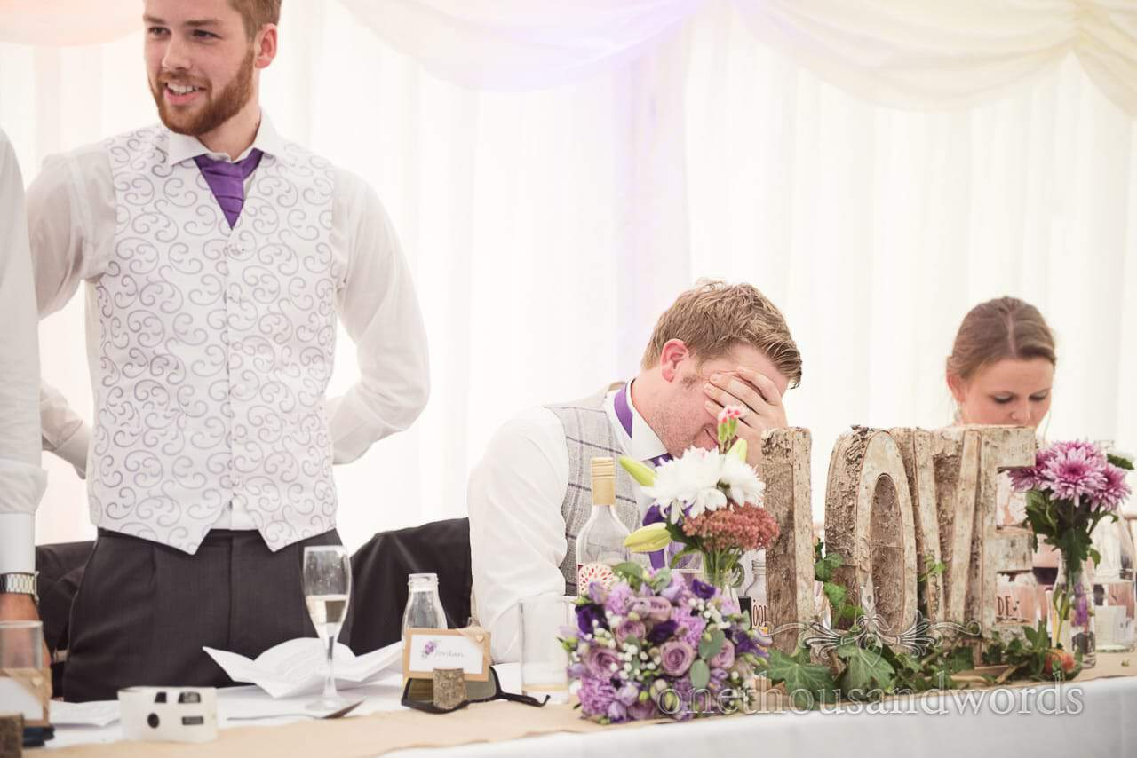 Groom holds his head in his hands during best men's speech at marquee wedding