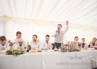 Groom raises a toast during wedding speech at marquee wedding in Dorset