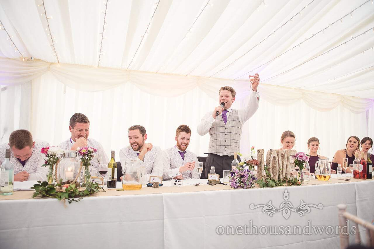 Groom raises a toast during wedding speech at marquee wedding in Dorset