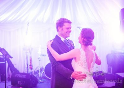 Groom smiles during first dance under blue disco lighting in wedding marquee