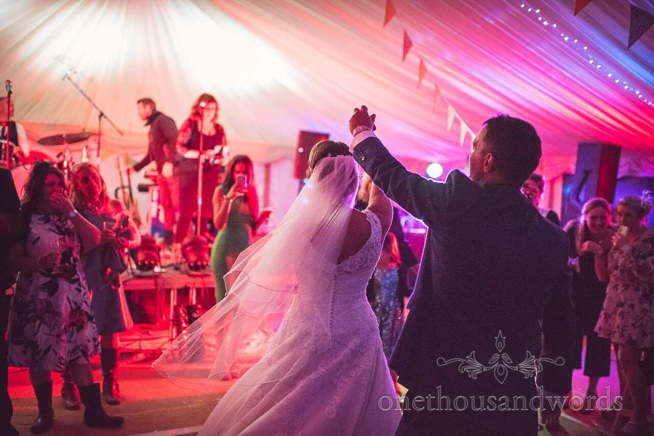 Groom twirls bride during wedding first dance in wedding marquee in Dorset