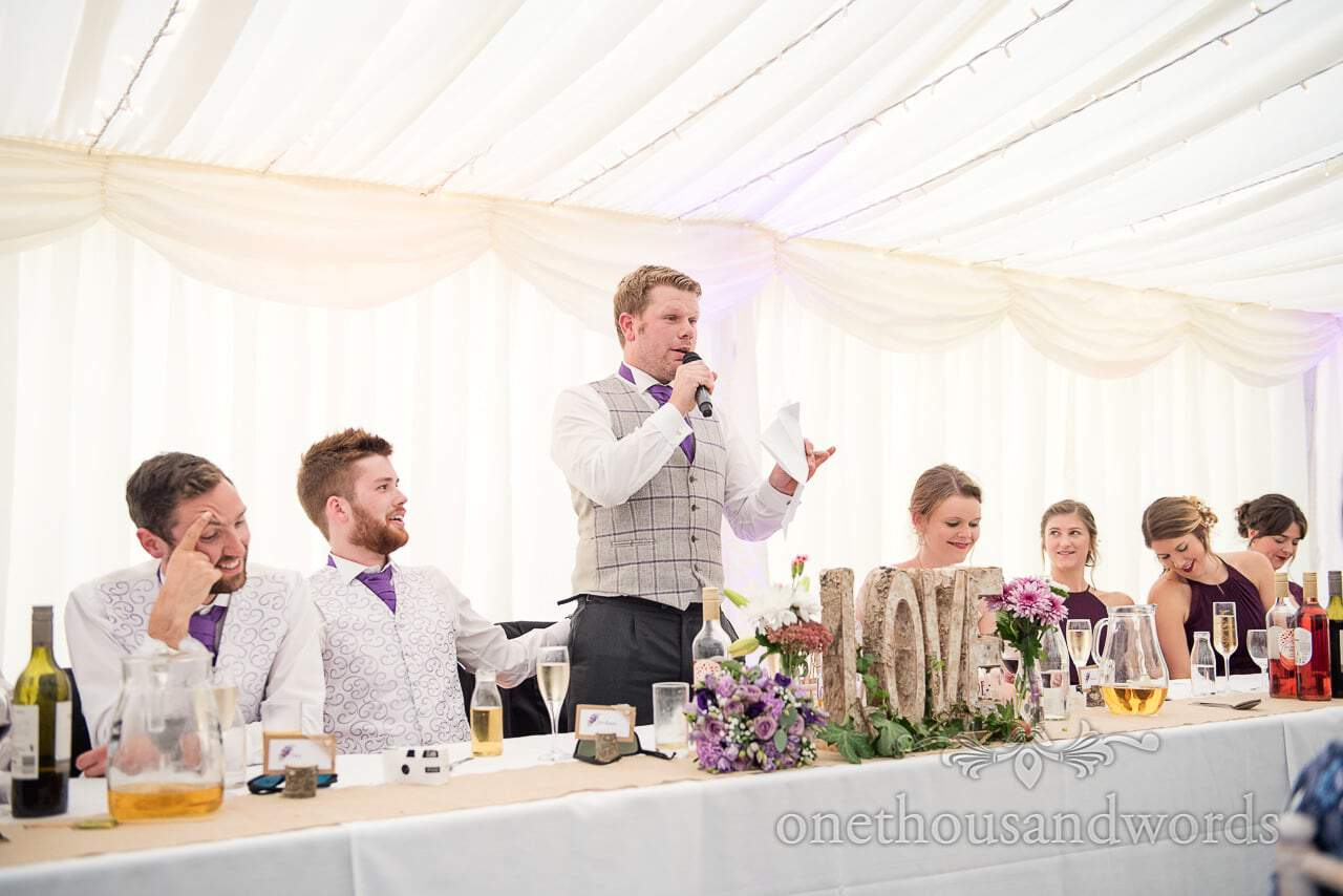 Grooms speech in front of wooden love sign at top table in marquee wedding