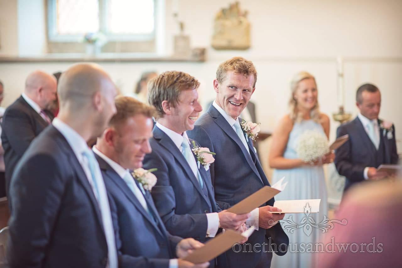 Groomsmen in blue suits laugh during Dorset Wedding Photographers Wedding ceremony