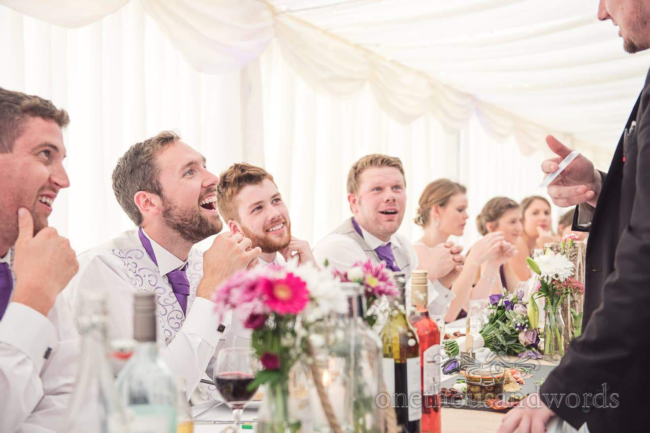 Groomsmen laugh at wedding magicians card trick at marquee wedding in Dorset