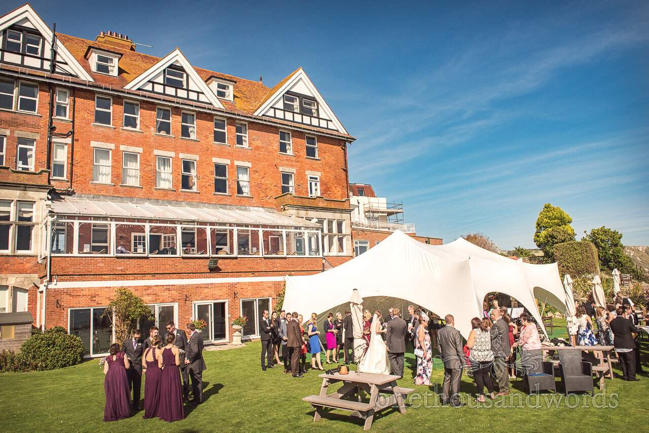 Guests and bridal party enjoy sunshine on lawn at Grand Hotel Wedding Photographs