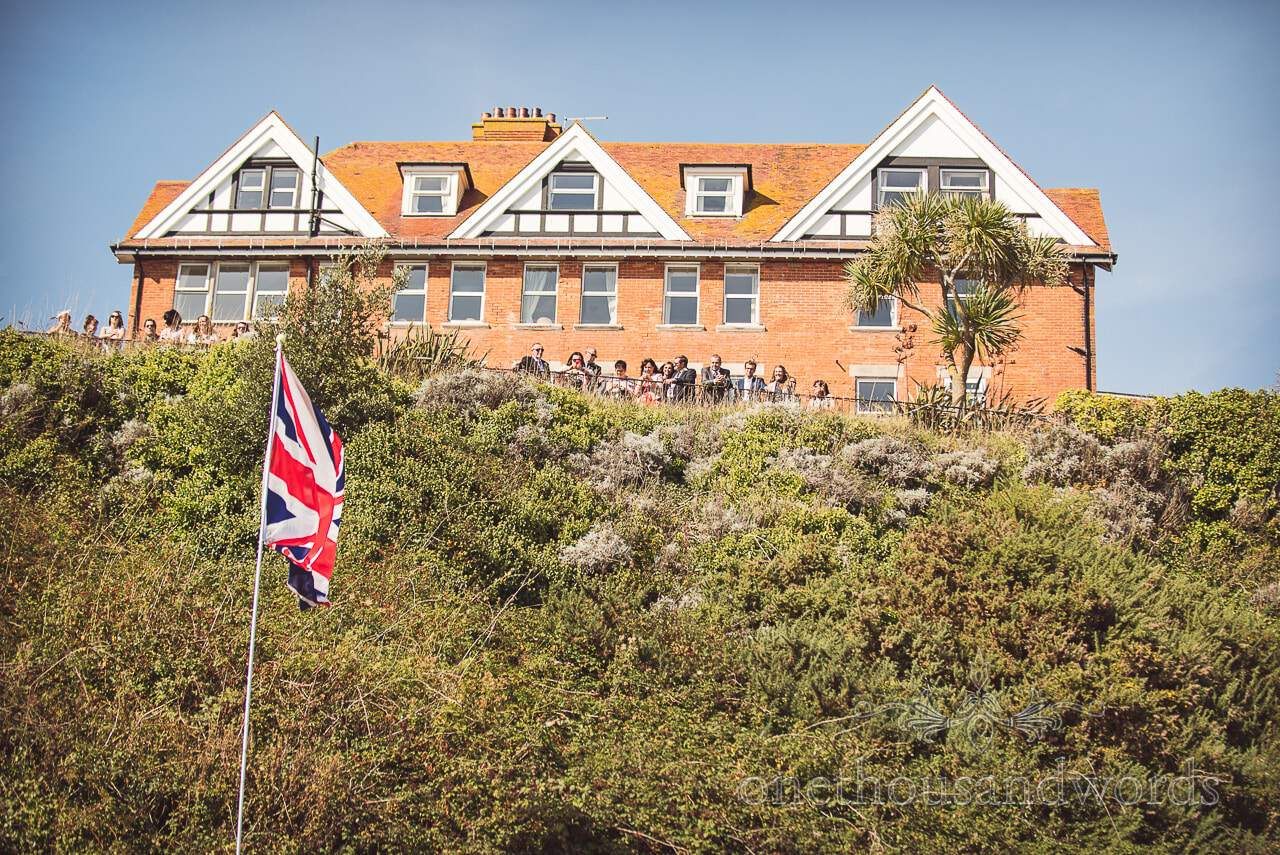Guests look on from cliff top garden at Grand Hotel Wedding Photographs