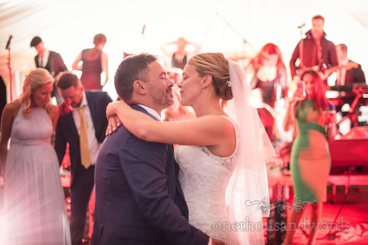 Look of love between bride and groom during first dance in wedding marquee