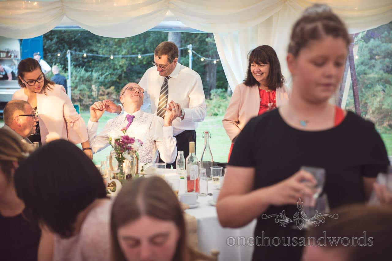 Male wedding guests embrace at marquee wedding evening reception