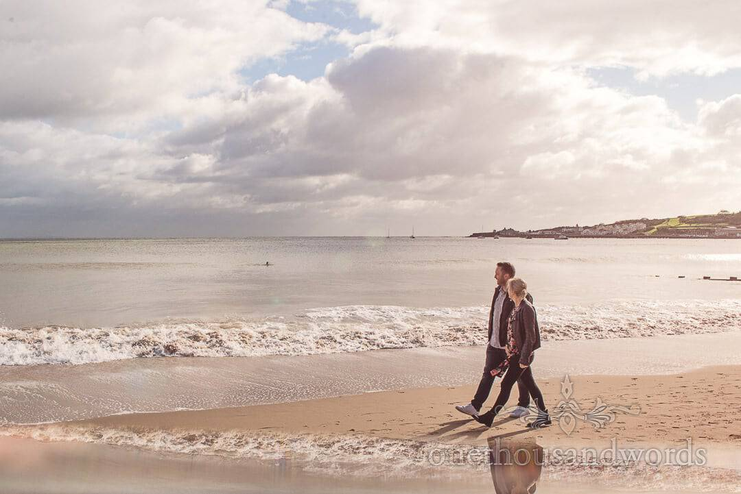 Newly engaged couple walking in the sun on Swanage beach