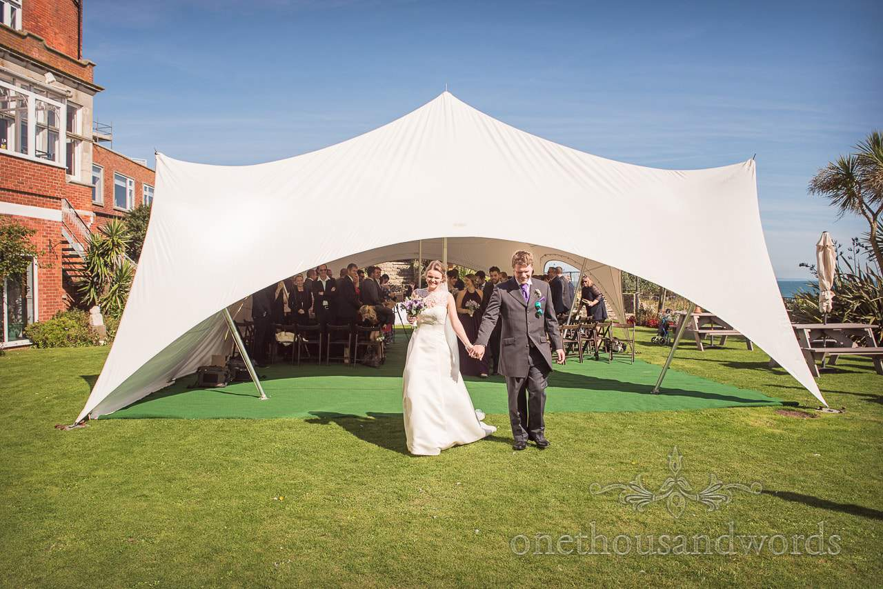 Newlyweds emerge from stretch tent on lawn at Grand Hotel Wedding Photographs