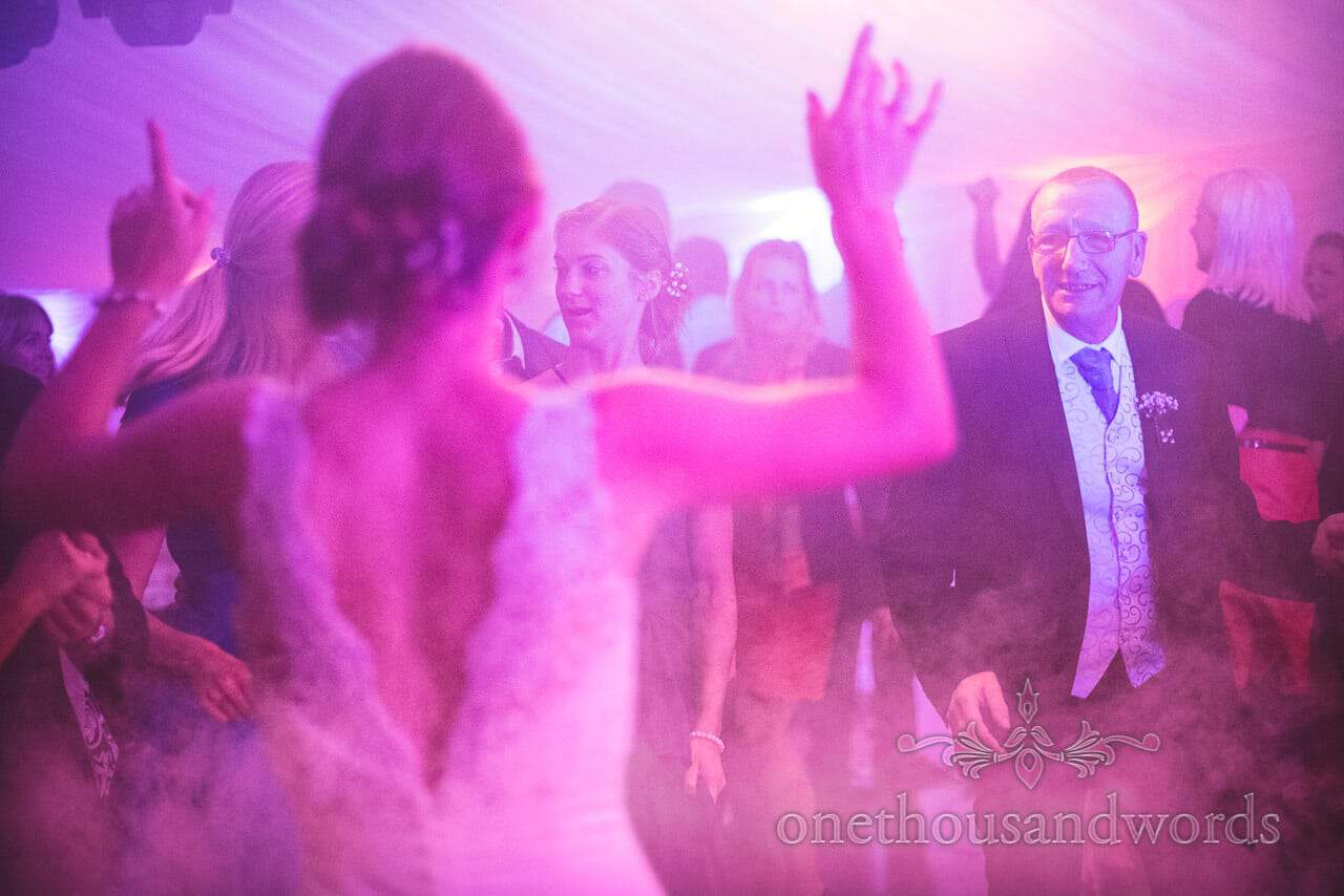 Wedding dancing in smoke under coloured disco lights at Swanage Marquee wedding