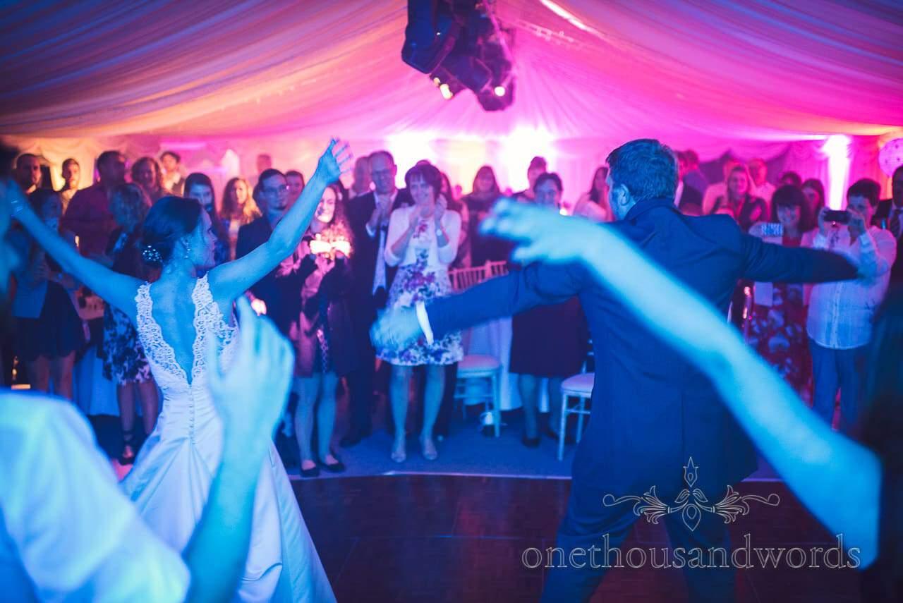 Wedding dancing under coloured disco lights at marquee wedding in Dorset