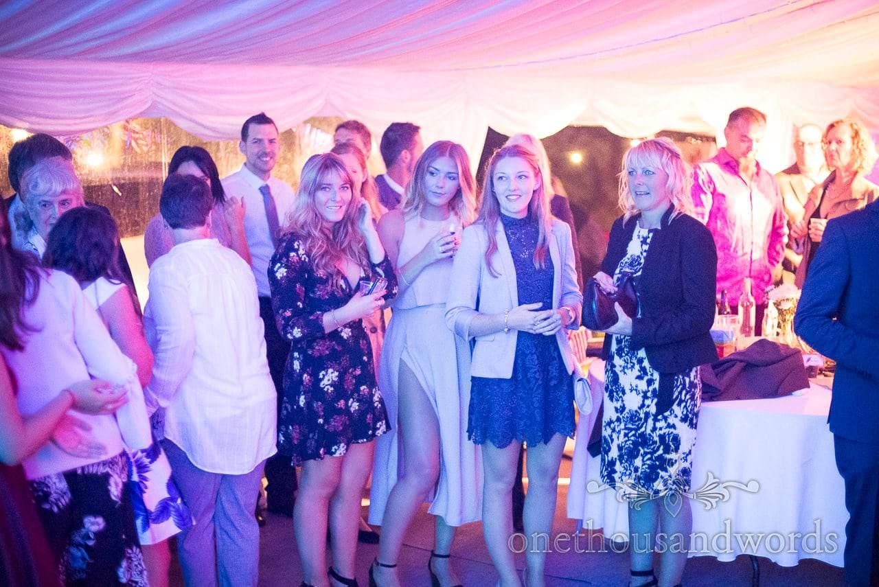 Wedding evening guests around dance floor under blue wedding disco lights