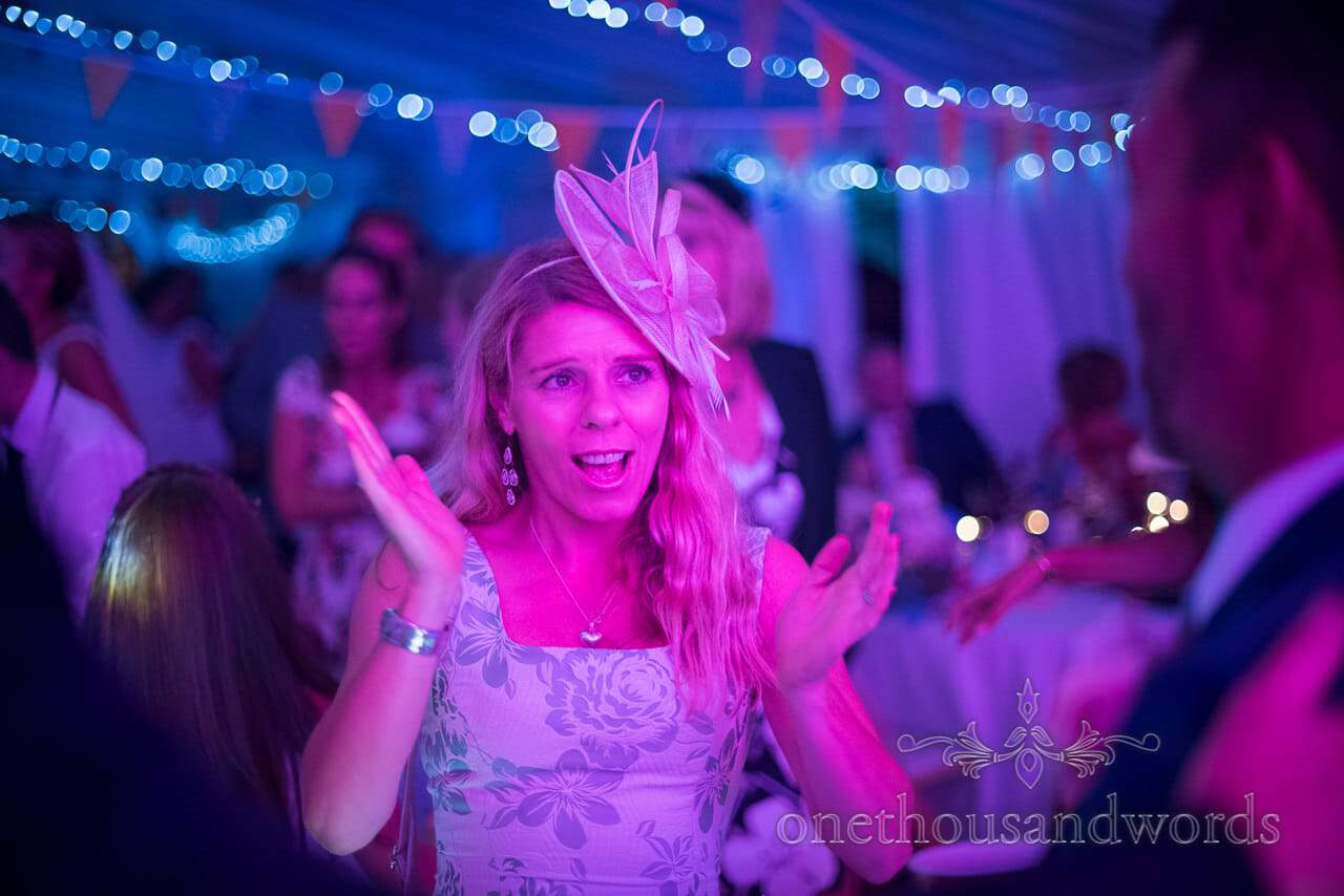 Wedding guest in fascinator dances in disco lights at Dorset wedding photographers wedding