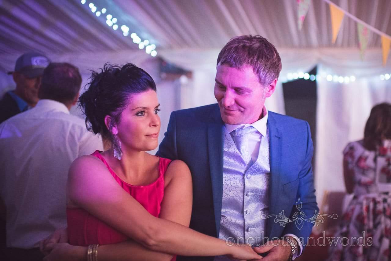 Wedding guests jive dance in wedding marquee evening reception in Dorset