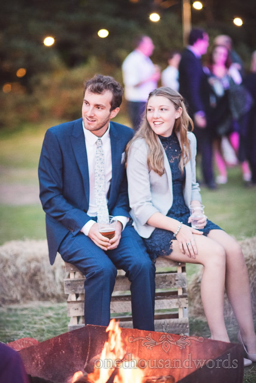 Wedding guests sit by the fire at wedding evening reception in Dorset