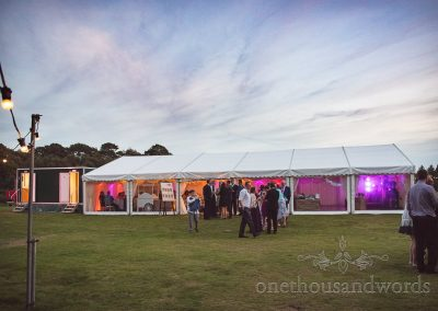 Wedding marquee in countryside evening with festoon lighting and coloured lights