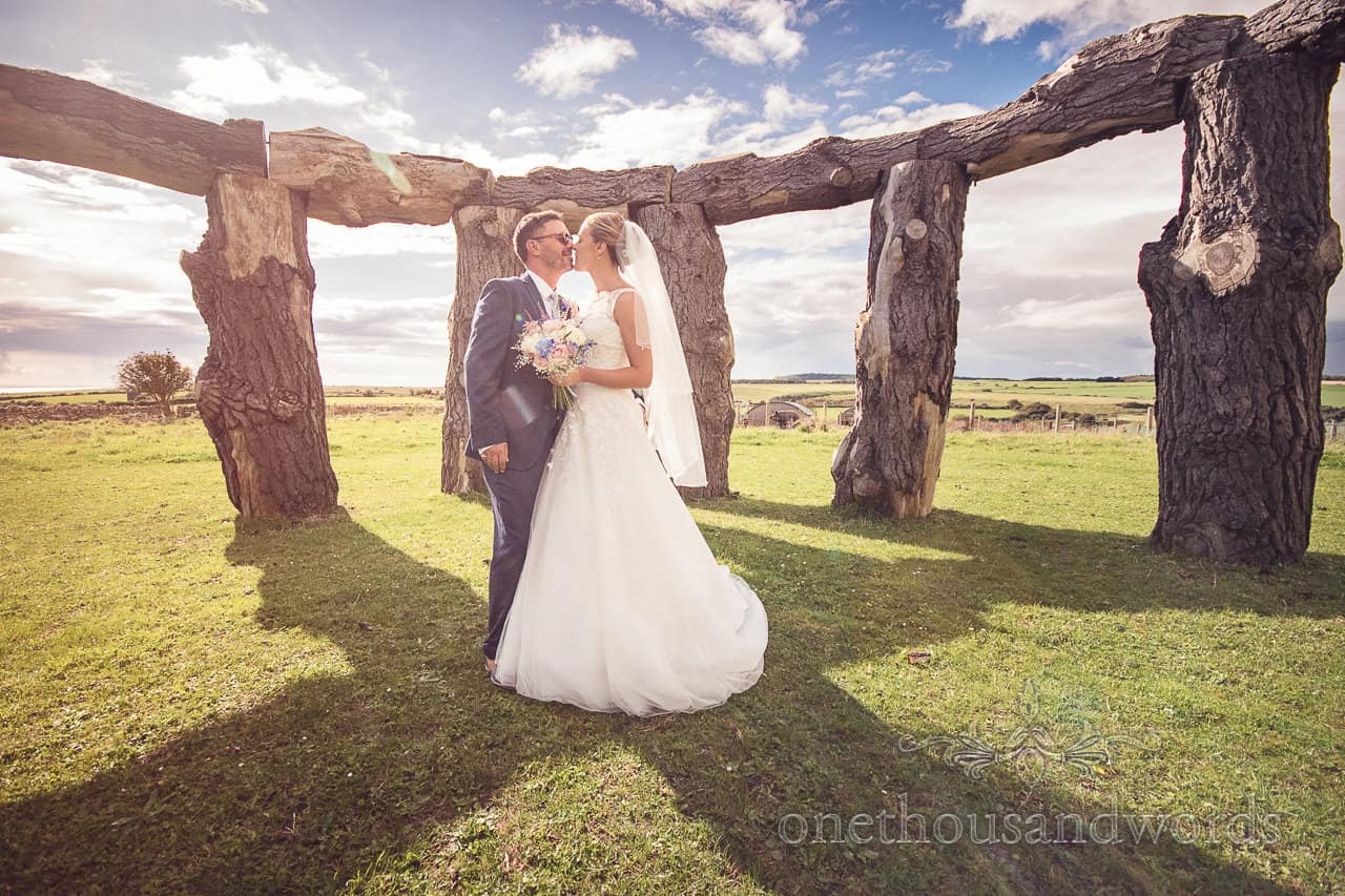 Wedding photographer groom and bride kiss in woodhenge in Dorset countryside