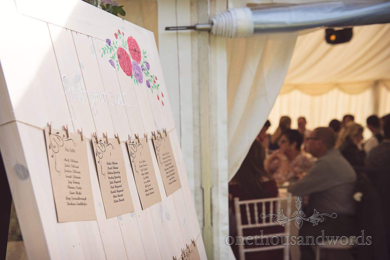 Wedding table plan with recycled paper pegged to string on wooden backing