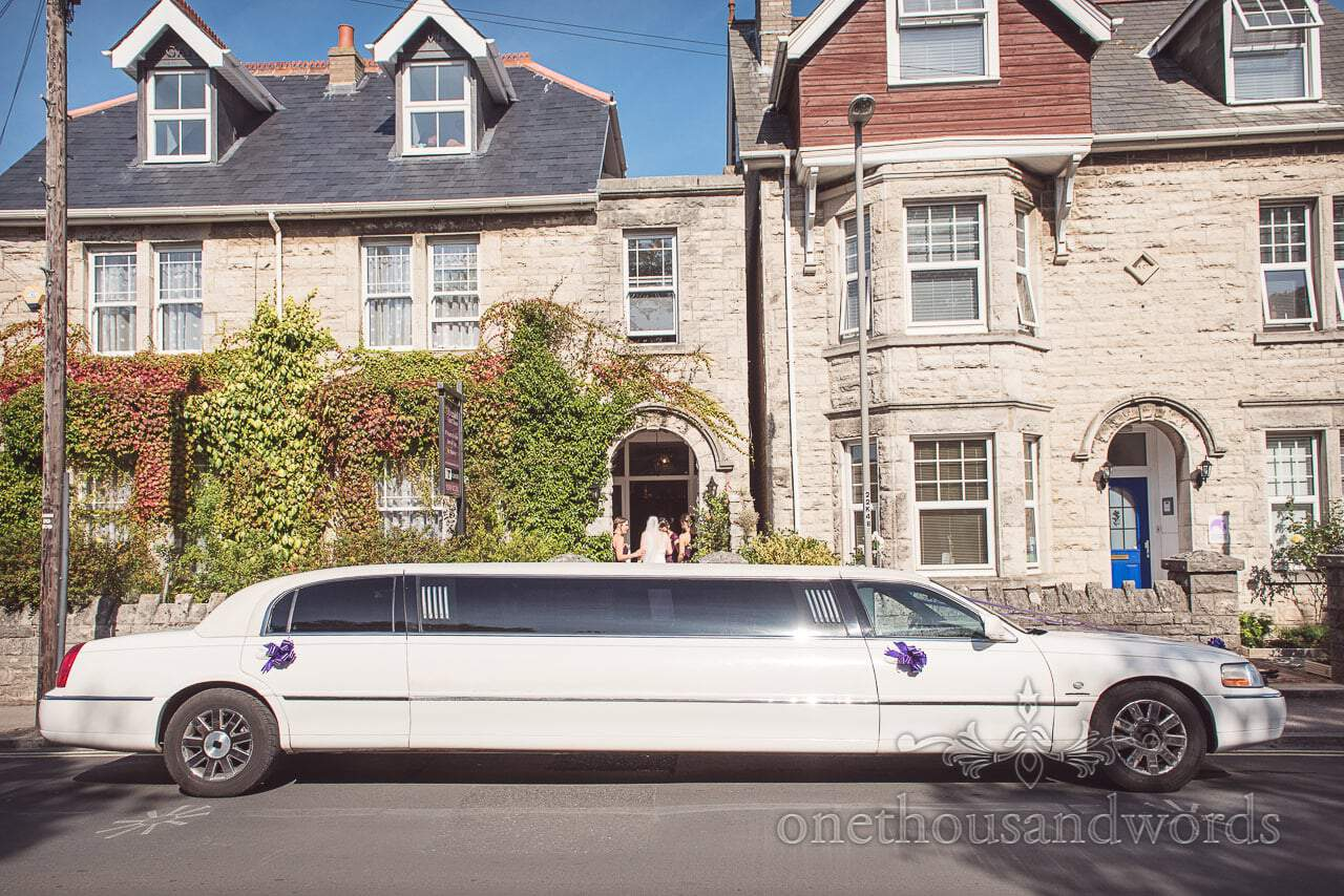 White stretch limousine waits for the bridal party before Grand Hotel Wedding Photographs