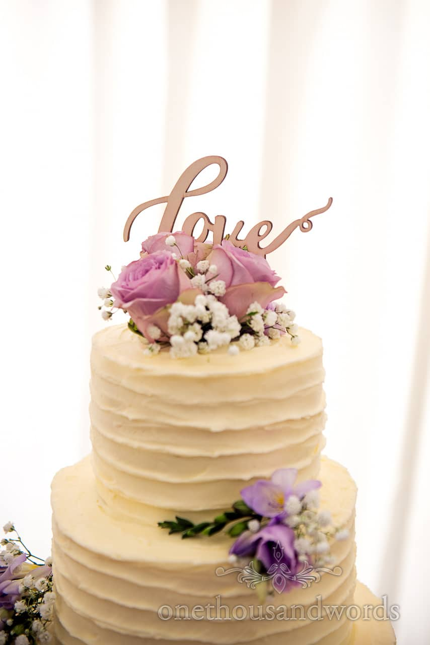 Wooden love sign on top of iced wedding cake with countryside flowers