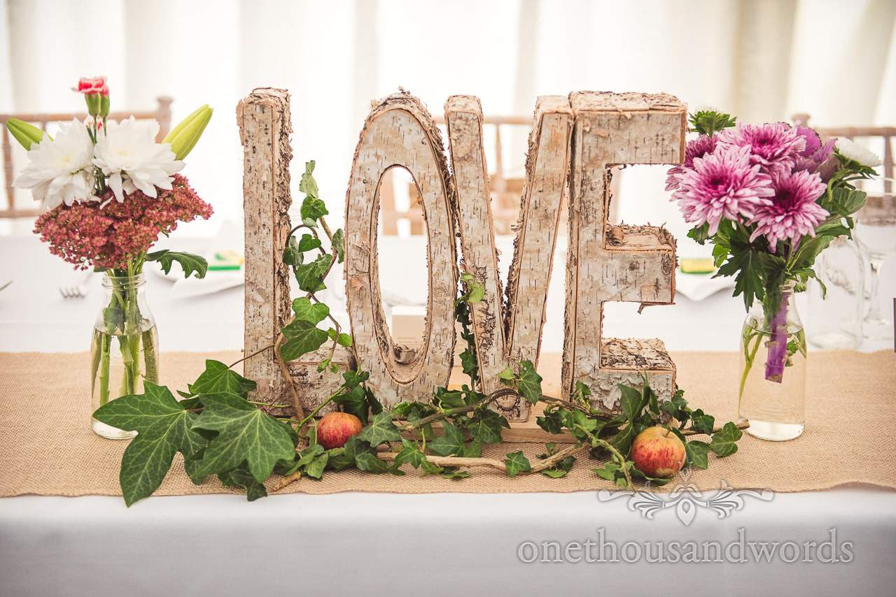 Wooden tree bark love sign with countryside flowers, ivy and apples at marquee wedding