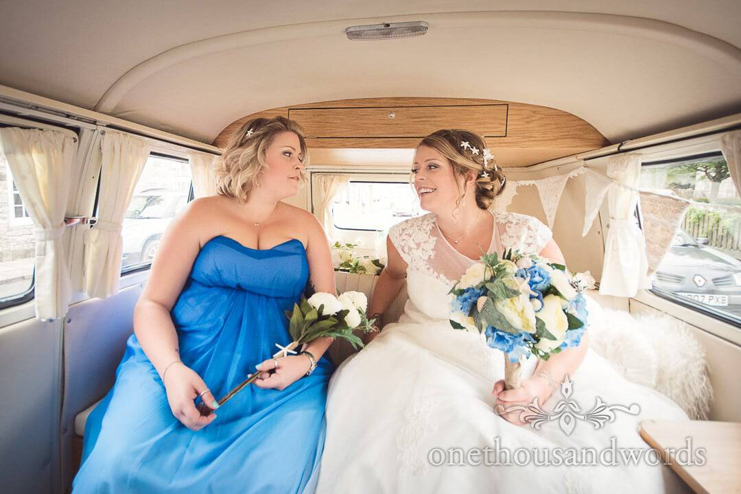 Bride and sister in blue bridesmaids dress laughing in classic VW wedding van