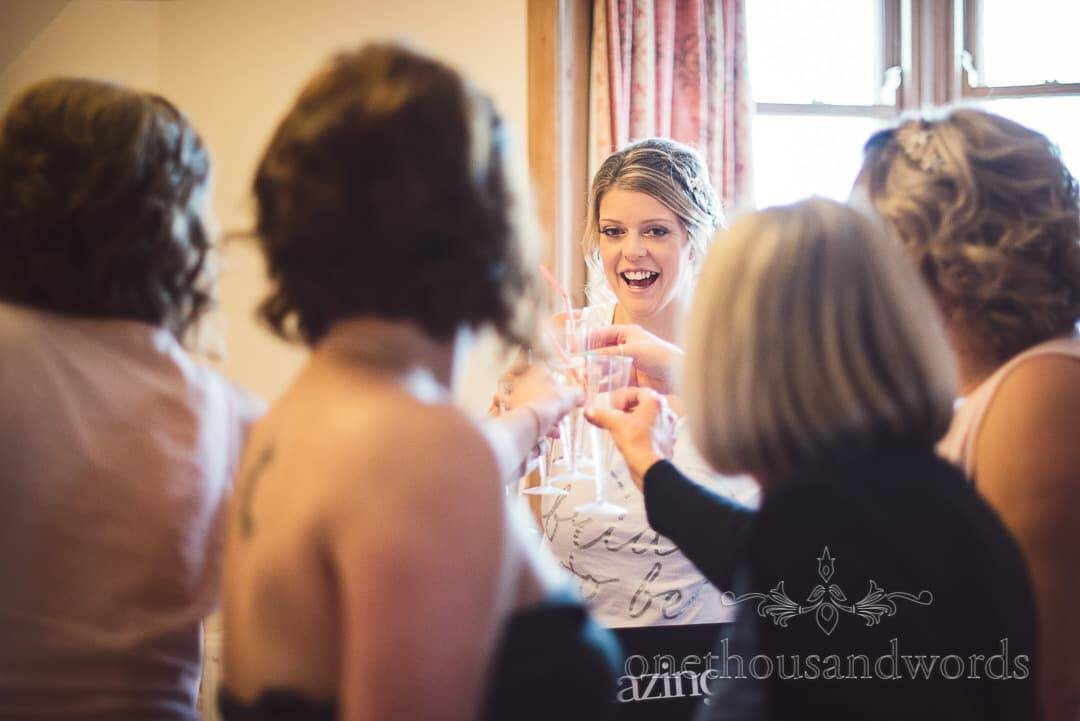 Bridal party raise a toast during bridal preparations on wedding morning in Dorset