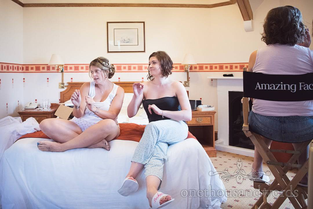 Bride and bridesmaid dance on hotel bed as wedding make-up is applied