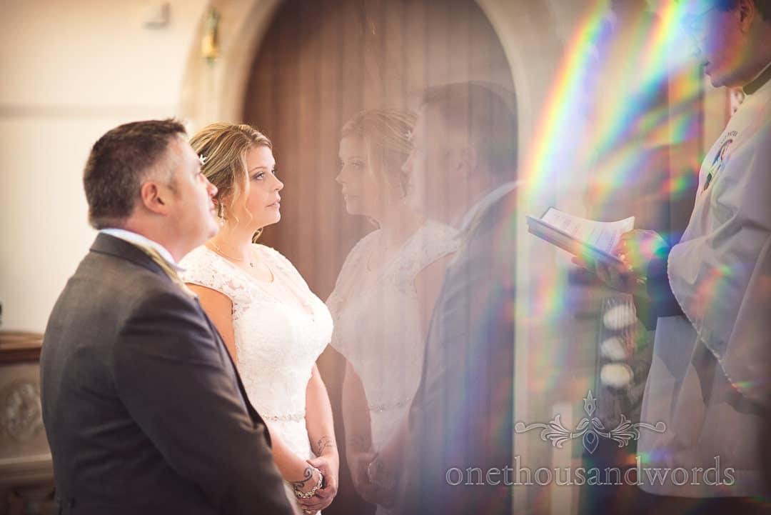 Bride and groom are blessed during wedding ceremony with prism reflections