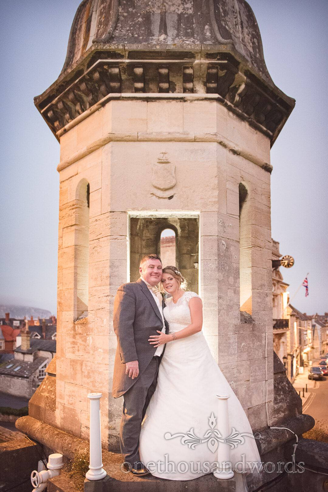 Bride and groom by Purbeck stone turret overlooking Swanage town at night
