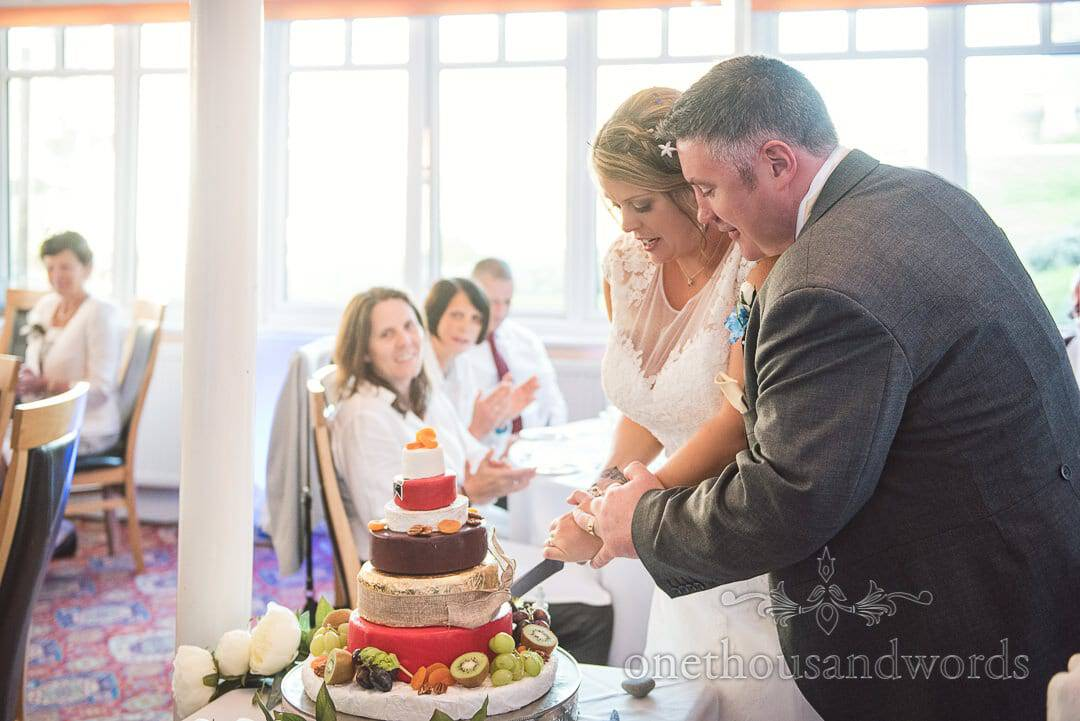 Bride and groom cut wedding cake made from cheese wheels at Dorset Hotel wedding