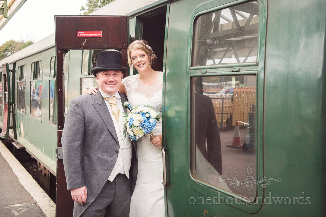 Bride and groom in top hat enter steam train at Swanage railway station