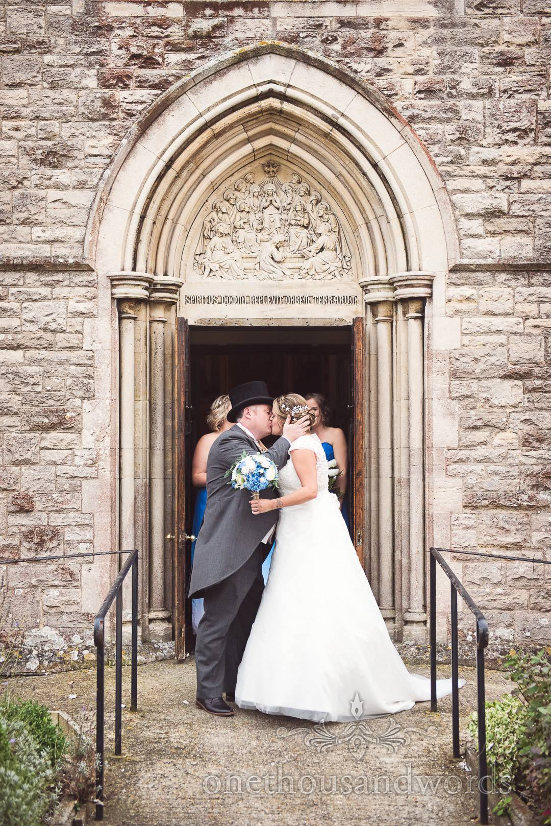 Bride and groom kiss outside Swanage Catholic church with stone archway door