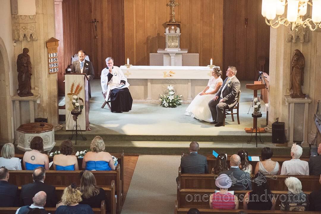 Bride and groom listen to Catholic readings in front of altar at Catholic church wedding