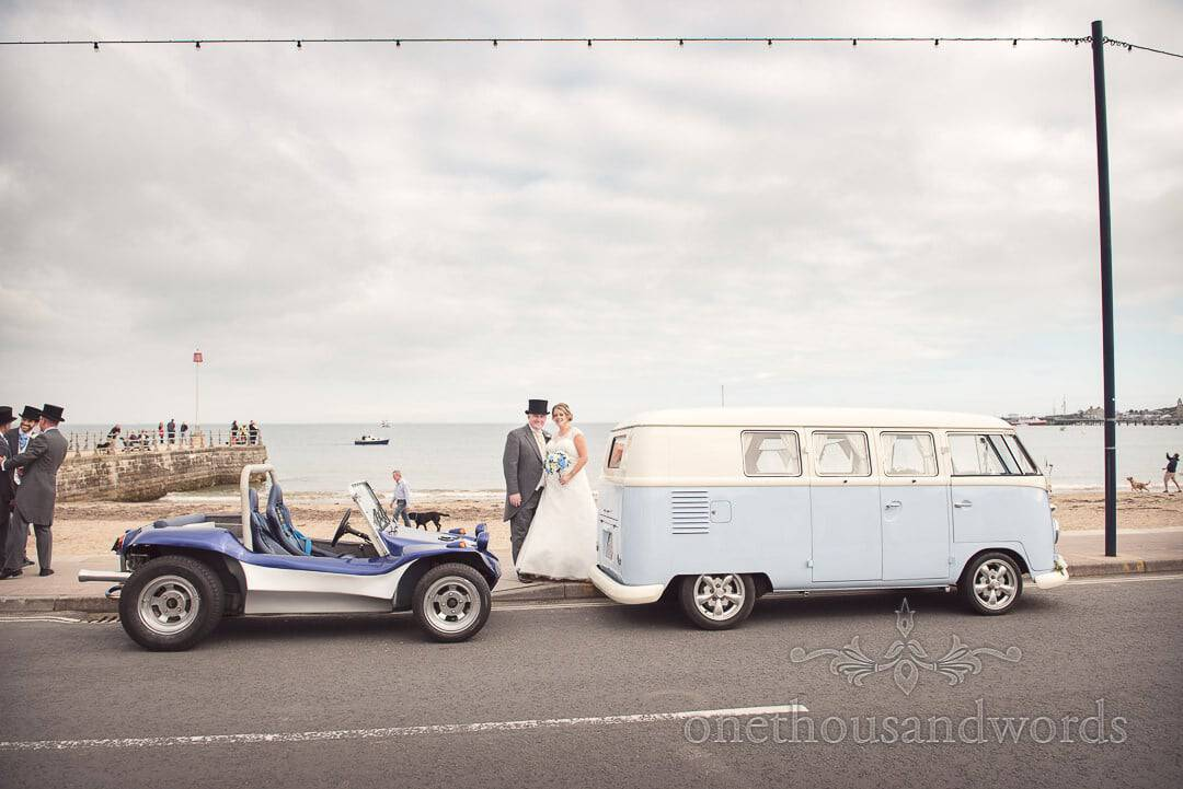 Bride and groom on Swanage Beach with VW van and VW beach buggy on wedding day