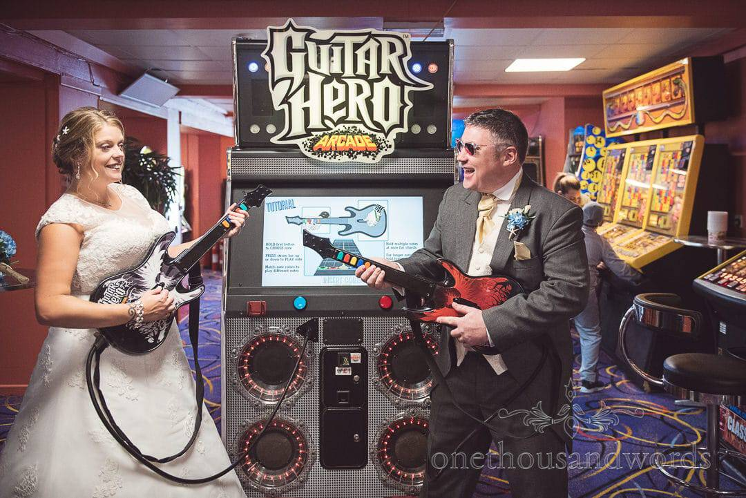 Bride and groom play Guitar Hero on wedding day in sea side arcades