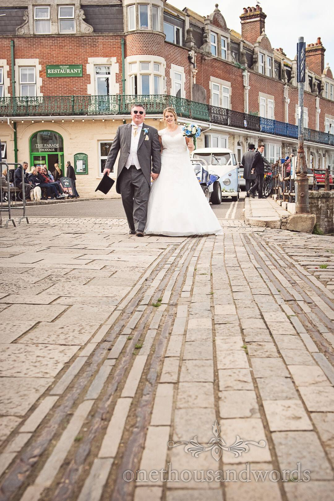Bride and groom walk along old stone cart tracks by the sea side in Swanage, Dorset