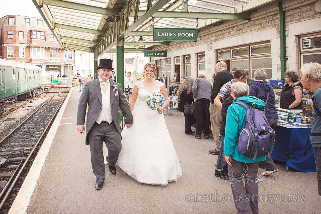 Bride and groom walk along platform at Swanage steam railway station in Dorset