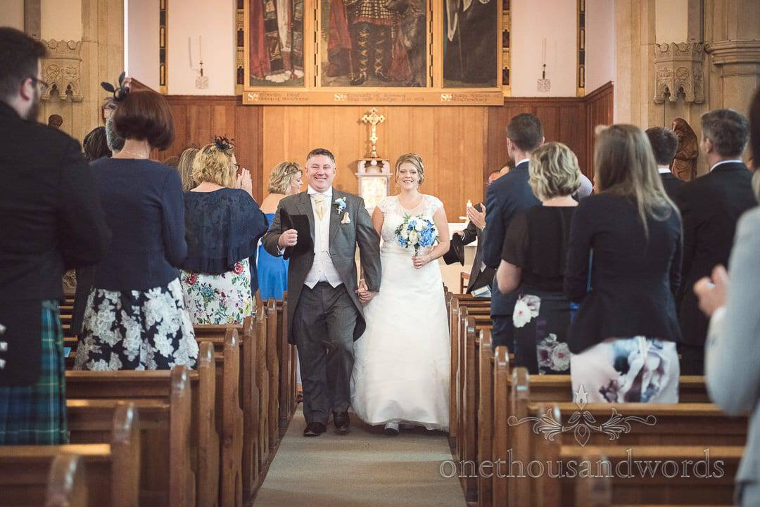 Bride and groom walk down aisle at Swanage Catholic Church wedding ceremony