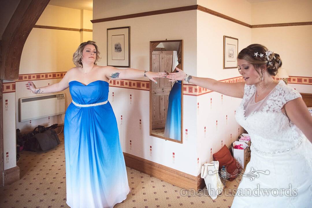 Bride and sister sing and dance in Hotel room on morning before wedding ceremony