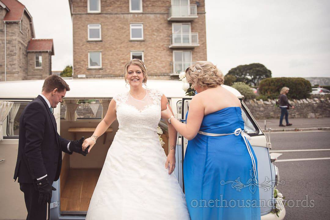 Bride exits VW wedding van outside Swanage church by the sea in Dorset