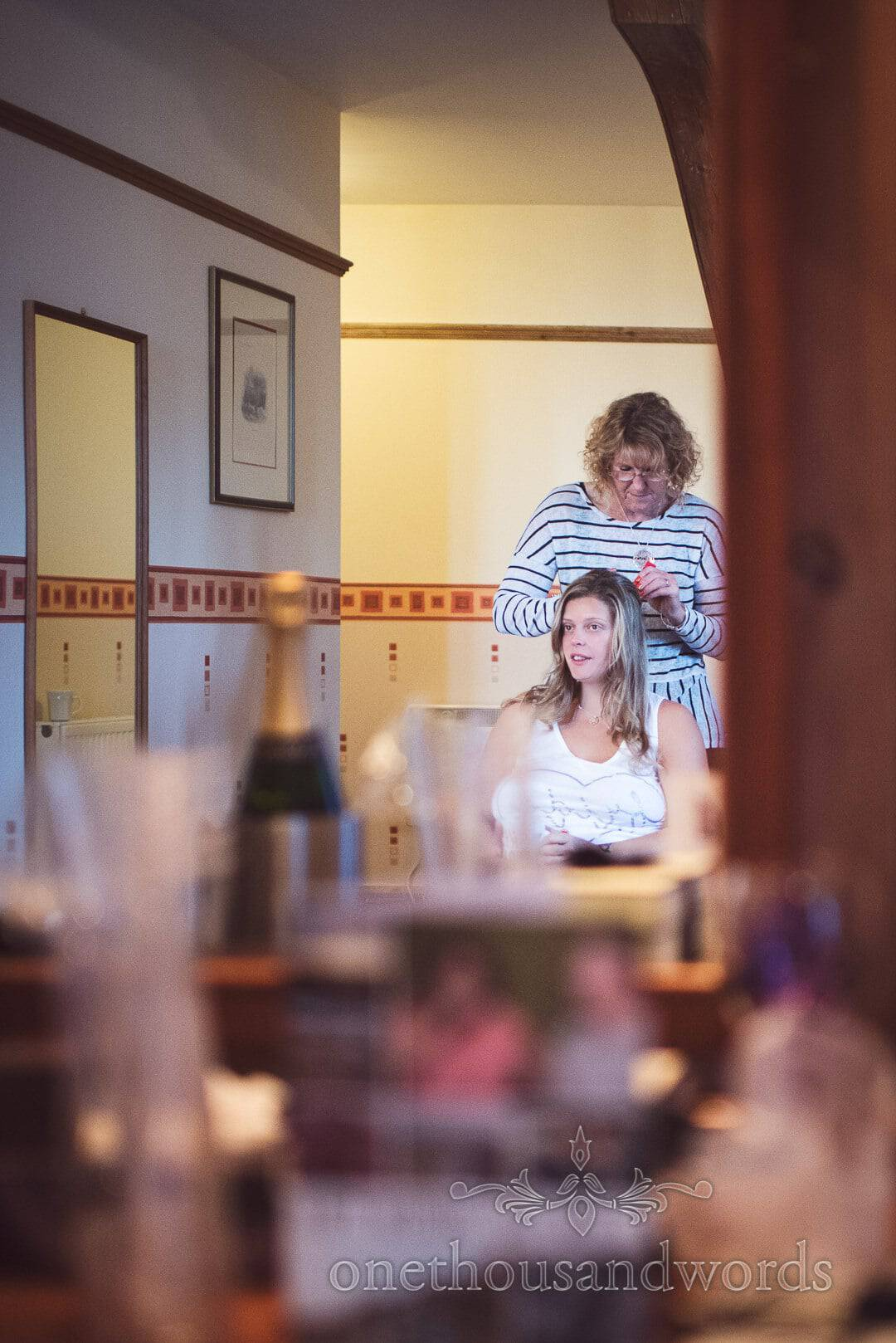 Bride has wedding hair styled in mirror at Purbeck House Hotel wedding morning