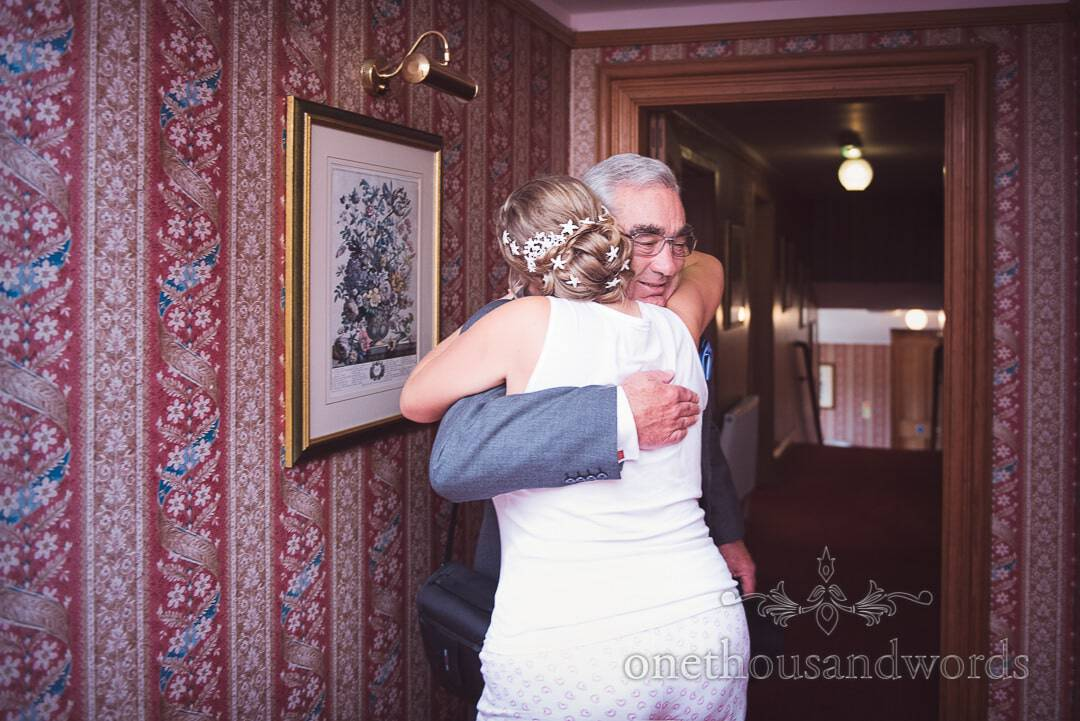 Bride hugs step father on wedding morning in Purbeck House Hotel in Swanage