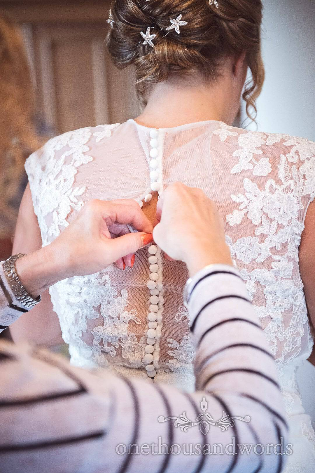 Bride is buttoned into white lace detailed wedding dress on wedding morning in Dorset