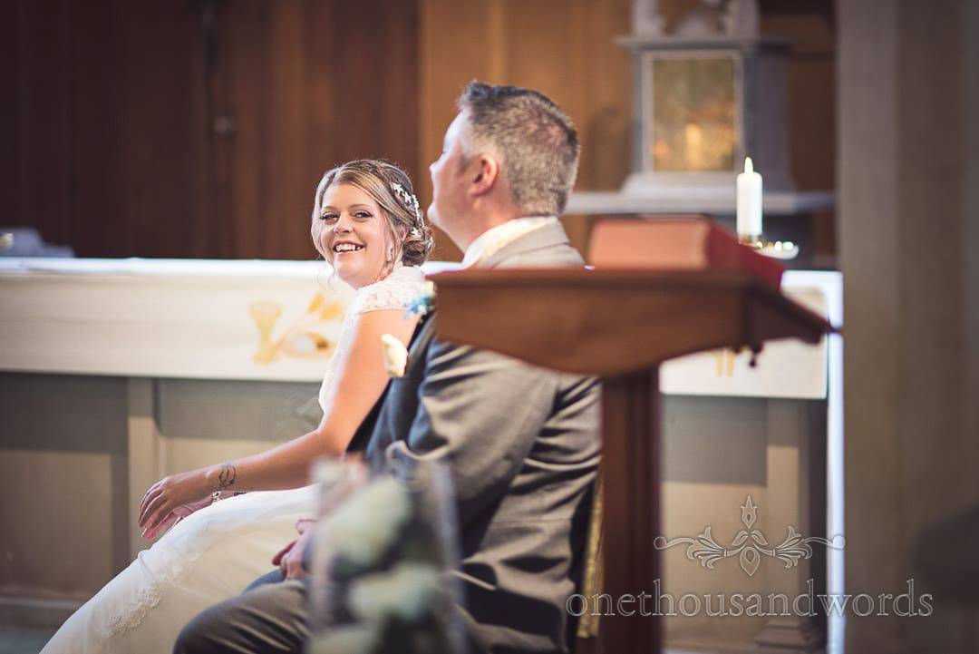 Bride laughs at groom during Swanage Catholic Church wedding ceremony