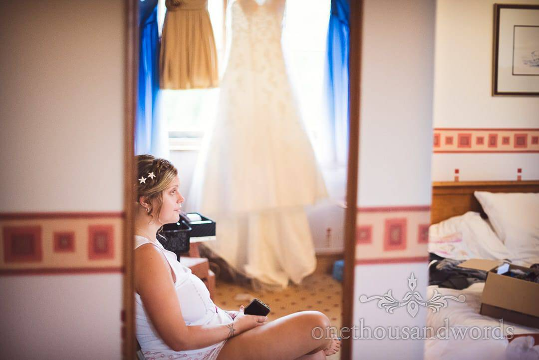 Bride relaxes in Purbeck House Hotel room on wedding morning in mirror with dresses