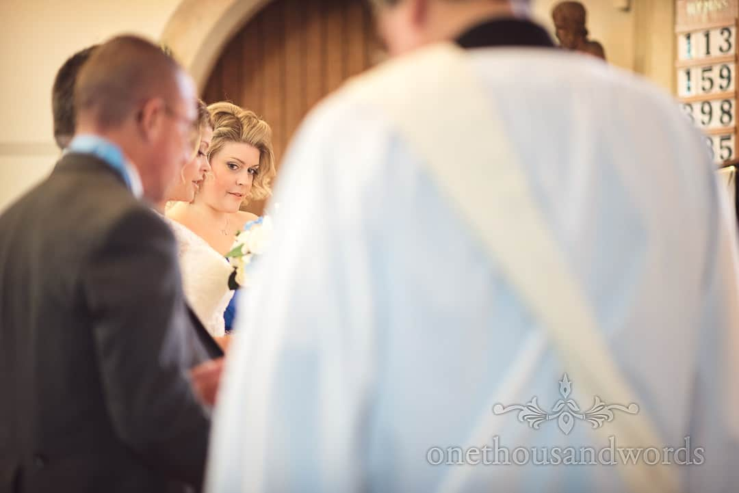 Bride's sister looks across wedding part during Catholic wedding ceremony
