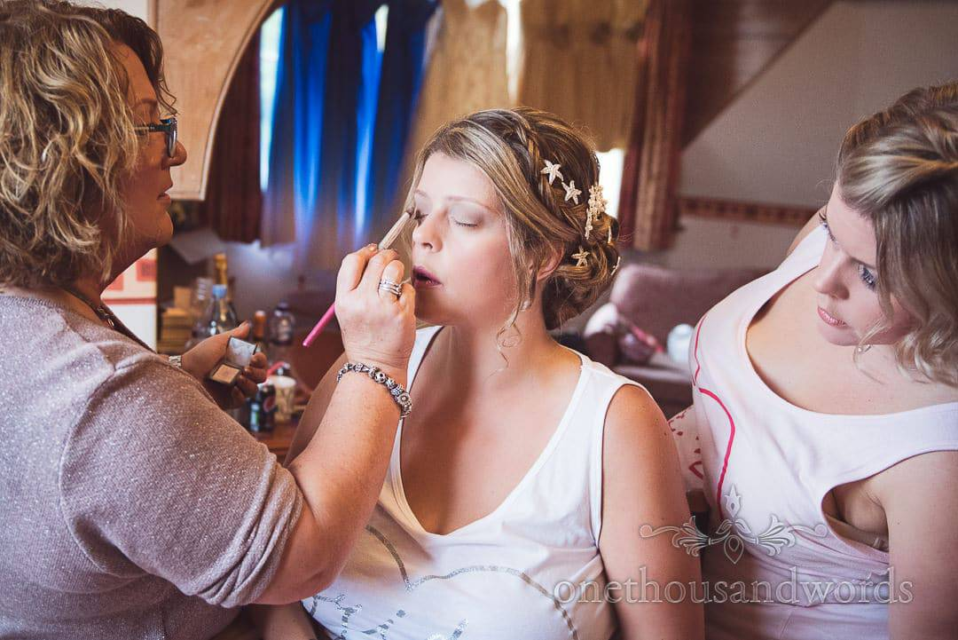 Bride's twin sister examines bridal make up application on wedding morning in Swanage
