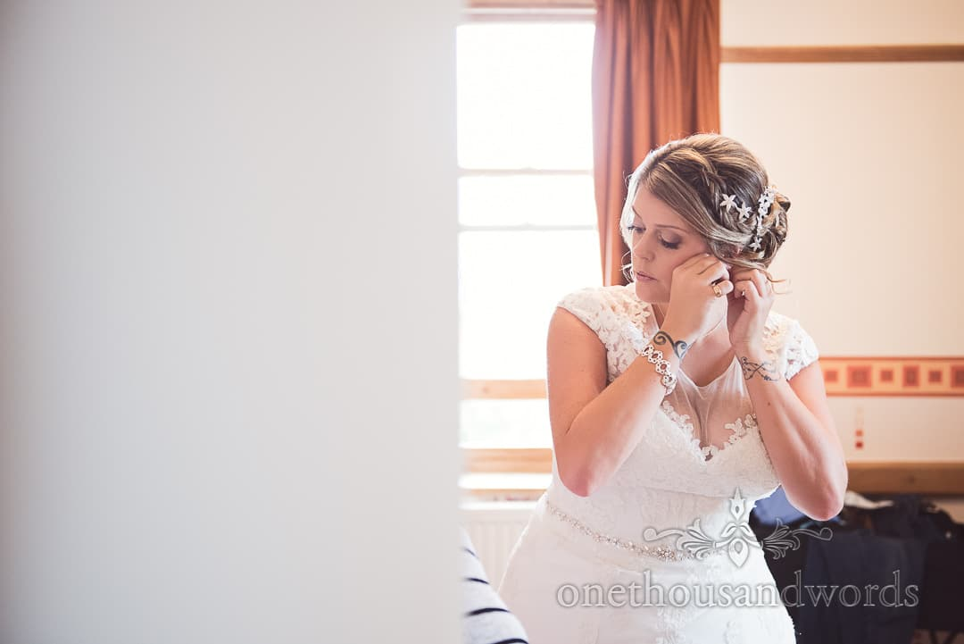 Bride with wrist tattoos in white wedding dress puts in earrings on wedding morning